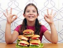 Μικρό κορίτσι με τα χάμπουργκερ και τα εντάξει σημάδια χεριών Στοκ Εικόνα