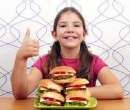 Μικρό κορίτσι με τα χάμπουργκερ και τον αντίχειρα επάνω Στοκ φωτογραφία με δικαίωμα ελεύθερης χρήσης