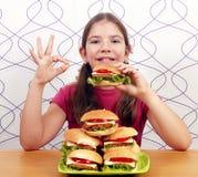 Μικρό κορίτσι με τα χάμπουργκερ και το εντάξει σημάδι χεριών Στοκ Εικόνα