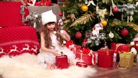 Μικρό κορίτσι με τα δώρα, έκπληξη Χριστουγέννων, παιδικά παιχνίδια Α στο σπίτι στη Παραμονή Χριστουγέννων, κοστούμι καρναβαλιού π απόθεμα βίντεο