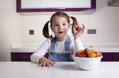 Μικρό κορίτσι με την ντομάτα αχλαδιών κερασιών στο χέρι της Στοκ φωτογραφία με δικαίωμα ελεύθερης χρήσης