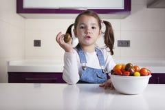 Μικρό κορίτσι με την ντομάτα κερασιών στο χέρι της Στοκ φωτογραφία με δικαίωμα ελεύθερης χρήσης