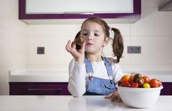 Μικρό κορίτσι με την ντομάτα κερασιών στο χέρι της Στοκ φωτογραφίες με δικαίωμα ελεύθερης χρήσης