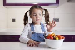 Μικρό κορίτσι με την ντομάτα κερασιών στο χέρι της Στοκ Φωτογραφίες