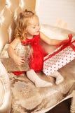 Μικρό κορίτσι με την ξανθή σγουρή τοποθέτηση τρίχας κοντά στο χριστουγεννιάτικο δέντρο με Στοκ Εικόνα