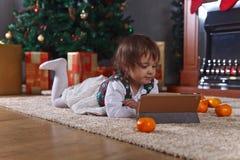 Μικρό κορίτσι με την ταμπλέτα στο δωμάτιο με τις διακοσμήσεις Χριστουγέννων Στοκ φωτογραφία με δικαίωμα ελεύθερης χρήσης