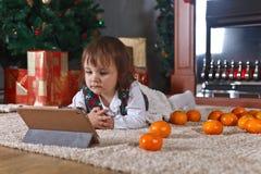 Μικρό κορίτσι με την ταμπλέτα στο δωμάτιο με τις διακοσμήσεις Χριστουγέννων Στοκ φωτογραφίες με δικαίωμα ελεύθερης χρήσης
