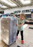 Μικρό κορίτσι με τη μεγάλη βαλίτσα στον αερολιμένα στοκ φωτογραφία