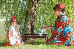 Μικρό κορίτσι με τη μητέρα στη συνεδρίαση κιμονό εκτός από τον πίνακα τσαγιού Στοκ Φωτογραφίες
