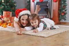 Μικρό κορίτσι με τη μητέρα στο δωμάτιο με τις διακοσμήσεις Χριστουγέννων Στοκ Εικόνες