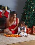 Μικρό κορίτσι με τη μητέρα στο δωμάτιο με τις διακοσμήσεις Χριστουγέννων Στοκ Φωτογραφία