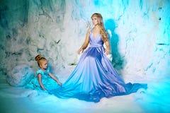 Μικρό κορίτσι με τη μητέρα στο φόρεμα πριγκηπισσών σε ένα υπόβαθρο ενός W Στοκ Φωτογραφία
