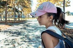 Μικρό κορίτσι με τη ρόδινη ΚΑΠ στο πάρκο στοκ εικόνες