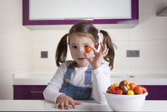 Μικρό κορίτσι με τη στρογγυλή ντομάτα κερασιών στο χέρι της Στοκ φωτογραφίες με δικαίωμα ελεύθερης χρήσης