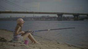 Μικρό κορίτσι με τη συνεδρίαση ράβδων αλιείας στην όχθη ποταμού απόθεμα βίντεο