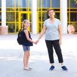 Μικρό κορίτσι με τη σχολική τσάντα ή satchel που περπατά στο σχολείο με τη γιαγιά στοκ φωτογραφίες