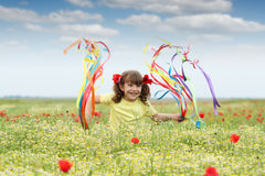 Μικρό κορίτσι με τις ζωηρόχρωμες κορδέλλες στον τομέα Στοκ Εικόνες