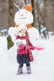 Μικρό κορίτσι με τις κόκκινες πλαστικές στάσεις φτυαριών ενάντια στο χιονάνθρωπο στοκ φωτογραφίες με δικαίωμα ελεύθερης χρήσης