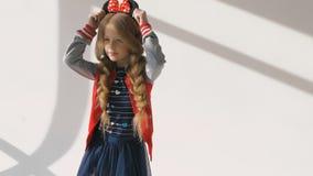 Μικρό κορίτσι με τις μακριές πλεξούδες σε ένα κόκκινο σακάκι Θέτοντας στο στούντιο, απόθεμα βίντεο