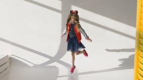 Μικρό κορίτσι με τις μακριές πλεξούδες σε ένα κόκκινο σακάκι Θέτοντας στο στούντιο, φιλμ μικρού μήκους