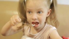 Μικρό κορίτσι με τις πλεξίδες που τρώει το γιαούρτι, χρήσιμα γαλακτοκομικά προϊόντα για τις παιδικές τροφές απόθεμα βίντεο