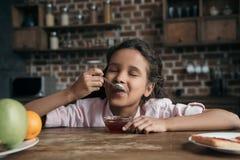 Μικρό κορίτσι με τις προσοχές ιδιαίτερες κατανάλωση της γλυκιάς μαρμελάδας από το κουταλάκι του γλυκού Στοκ φωτογραφία με δικαίωμα ελεύθερης χρήσης