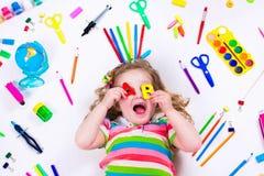 Μικρό κορίτσι με τις σχολικές προμήθειες Στοκ Φωτογραφίες
