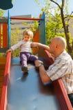 Μικρό κορίτσι με τον μπαμπά στην παιδική χαρά στοκ φωτογραφία