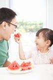 μικρό κορίτσι με τον πατέρα που τρώει τους καρπούς Στοκ εικόνα με δικαίωμα ελεύθερης χρήσης