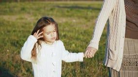Μικρό κορίτσι με τον περίπατο mom της στον αγροτικό δρόμο στο ηλιοβασίλεμα φιλμ μικρού μήκους