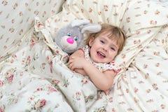 Μικρό κορίτσι με τους λαγούς παιχνιδιών στο κρεβάτι Στοκ εικόνα με δικαίωμα ελεύθερης χρήσης