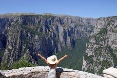 Μικρό κορίτσι με τους αντίχειρες επάνω στο φαράγγι Vikos άποψης Στοκ Εικόνα