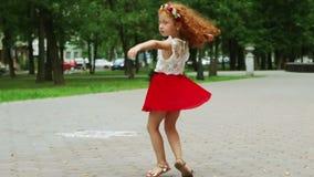 Μικρό κορίτσι με τους κόκκινους χορούς τρίχας στο πράσινο θερινό πάρκο απόθεμα βίντεο