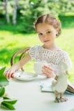 Μικρό κορίτσι με το άσπρο φλυτζάνι υπαίθριο Στοκ Φωτογραφία