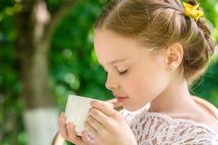 Μικρό κορίτσι με το άσπρο φλυτζάνι υπαίθριο Στοκ Εικόνες