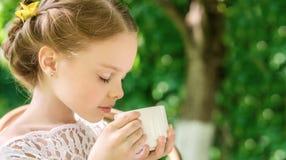 Μικρό κορίτσι με το άσπρο φλυτζάνι υπαίθριο Στοκ φωτογραφία με δικαίωμα ελεύθερης χρήσης