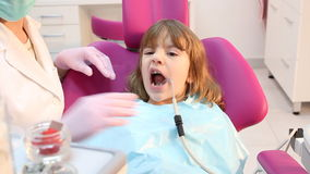 Μικρό κορίτσι με το ανοικτό στόμα κατά τη διάρκεια της επεξεργασίας διάτρυσης στον οδοντίατρο απόθεμα βίντεο