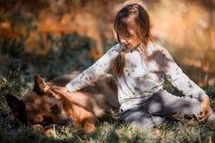 Μικρό κορίτσι με το γερμανικό σκυλί ποιμένων υπαίθριο στοκ φωτογραφία με δικαίωμα ελεύθερης χρήσης