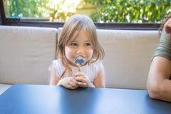 Μικρό κορίτσι με το κουτάλι στα χέρια που χαμογελά στο εστιατόριο Στοκ εικόνα με δικαίωμα ελεύθερης χρήσης
