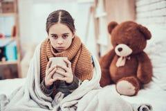 Μικρό κορίτσι με το κρύο στο μαντίλι και κάλυμμα με το καυτό ποτό στα χέρια στο σπίτι στοκ εικόνες με δικαίωμα ελεύθερης χρήσης