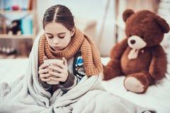 Μικρό κορίτσι με το κρύο στο μαντίλι και κάλυμμα με το καυτό ποτό στα χέρια στο σπίτι στοκ εικόνα
