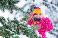 Μικρό κορίτσι με το παγάκι στο χιονώδες χειμερινό πάρκο Στοκ Εικόνες