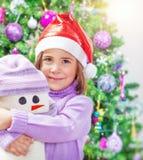 Μικρό κορίτσι με το παιχνίδι χιονανθρώπων Στοκ Εικόνες