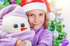 Μικρό κορίτσι με το παιχνίδι χιονανθρώπων Στοκ Φωτογραφίες