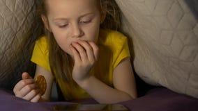 Μικρό κορίτσι με το τηλέφωνο και το μπισκότο απόθεμα βίντεο