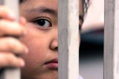 Μικρό κορίτσι με το φράκτη μετάλλων, που δεν αισθάνεται καμία ελευθερία Στοκ φωτογραφία με δικαίωμα ελεύθερης χρήσης