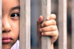 Μικρό κορίτσι με το φράκτη μετάλλων, που δεν αισθάνεται καμία ελευθερία Στοκ εικόνα με δικαίωμα ελεύθερης χρήσης