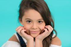 Μικρό κορίτσι με το χαμόγελο στο λατρευτό πρόσωπο στο μπλε υπόβαθρο Στοκ φωτογραφία με δικαίωμα ελεύθερης χρήσης