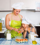 Μικρό κορίτσι με το mom στην κουζίνα Στοκ φωτογραφία με δικαίωμα ελεύθερης χρήσης