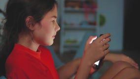 Μικρό κορίτσι με το smartphone που βρίσκεται σε ένα κρεβάτι, ώρα για ύπνο παίζοντας παιχνίδι online smartphone μικρών κοριτσιών σ απόθεμα βίντεο